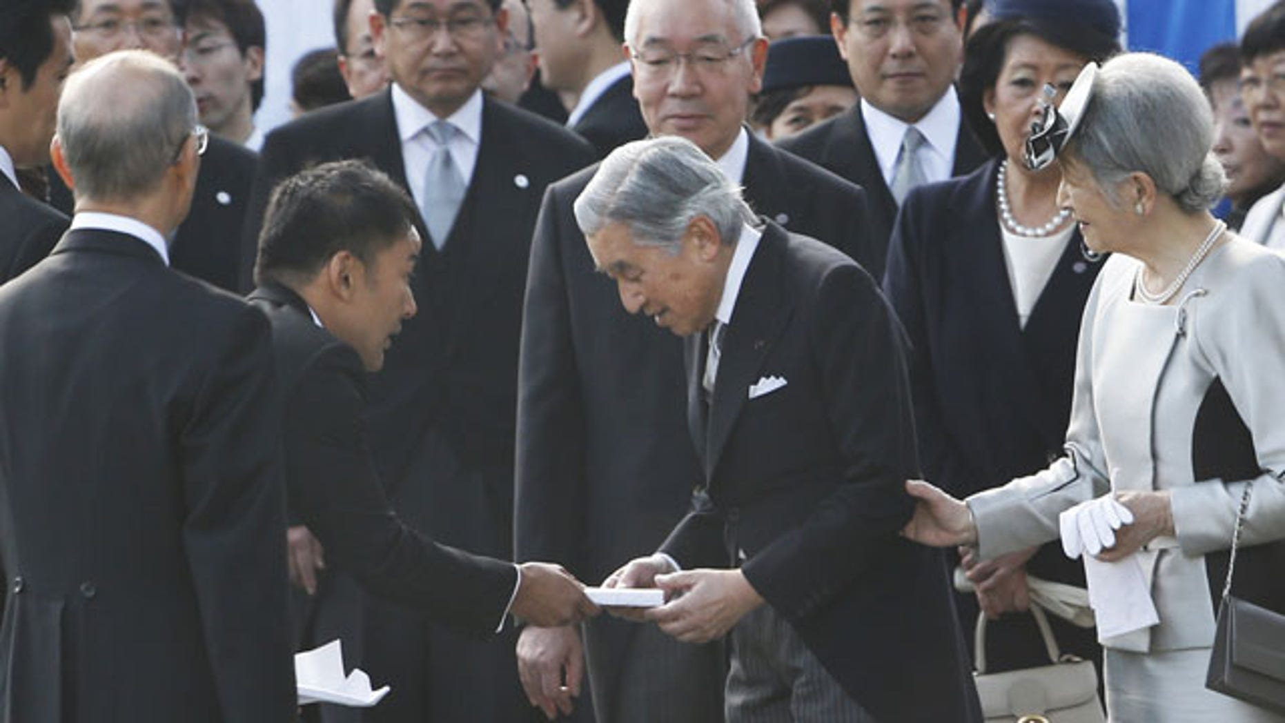 FILE - In this Thursday, Oct. 31, 2013 file photo, actor-turned-lawmaker Taro Yamamoto, second left, hands over a letter to Japan's Emperor Akihito, second right, as Empress Michiko, right, and chief steward Yutaka Kawashima, top center, look on during the autumn garden party at the Imperial Palace in Tokyo. The novice lawmaker has caused an uproar in Japan by doing something taboo: handing a letter to the emperor - a gesture considered both impolite and inappropriate. (AP Photo)