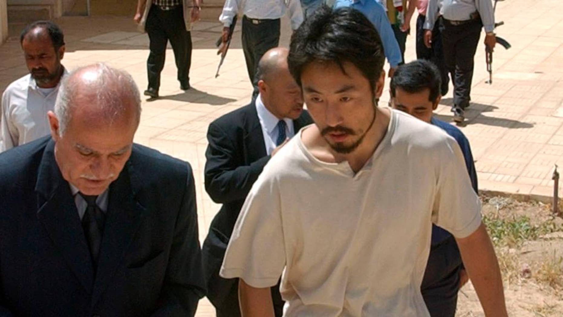 FILE - In this April 17, 2004 file photo, Japanese freelance journalist Jumpei Yasuda, right, is escorted after being released at Umm Al-Qura mosque in Baghdad, Iraq.  Worries are growing about the whereabouts of the freelance Japanese journalist, last heard from late June, 2015,  in Syria. It is not known why Yasuda, who has been reporting on the Middle East since 2002, has not been in contact or if he has been taken captive in the war-torn nation. (AP Photo/Muhammed Muheisen, File)