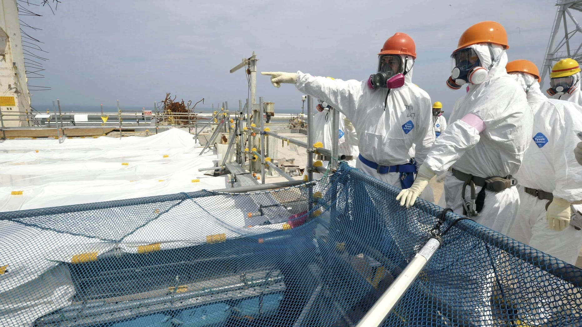 May 26, 2012: Japan's Environment and Nuclear Minister Goshi Hosono, second from left, inspects a pool containing spent fuel rods inside the No. 4 reactor building at Tokyo Electric Power Co. 's tsunami-crippled Fukushima Dai-ichi nuclear power plant in Okuma, Fukushima Prefecture, Japan, Saturday, May 26, 2012. The pool, located at the top of the building above the reactor, remains one of the plant's biggest risks due to its vulnerability to earthquakes. (AP Photo/Toshiaki Shimizu, Japan Pool) JAPAN OUT