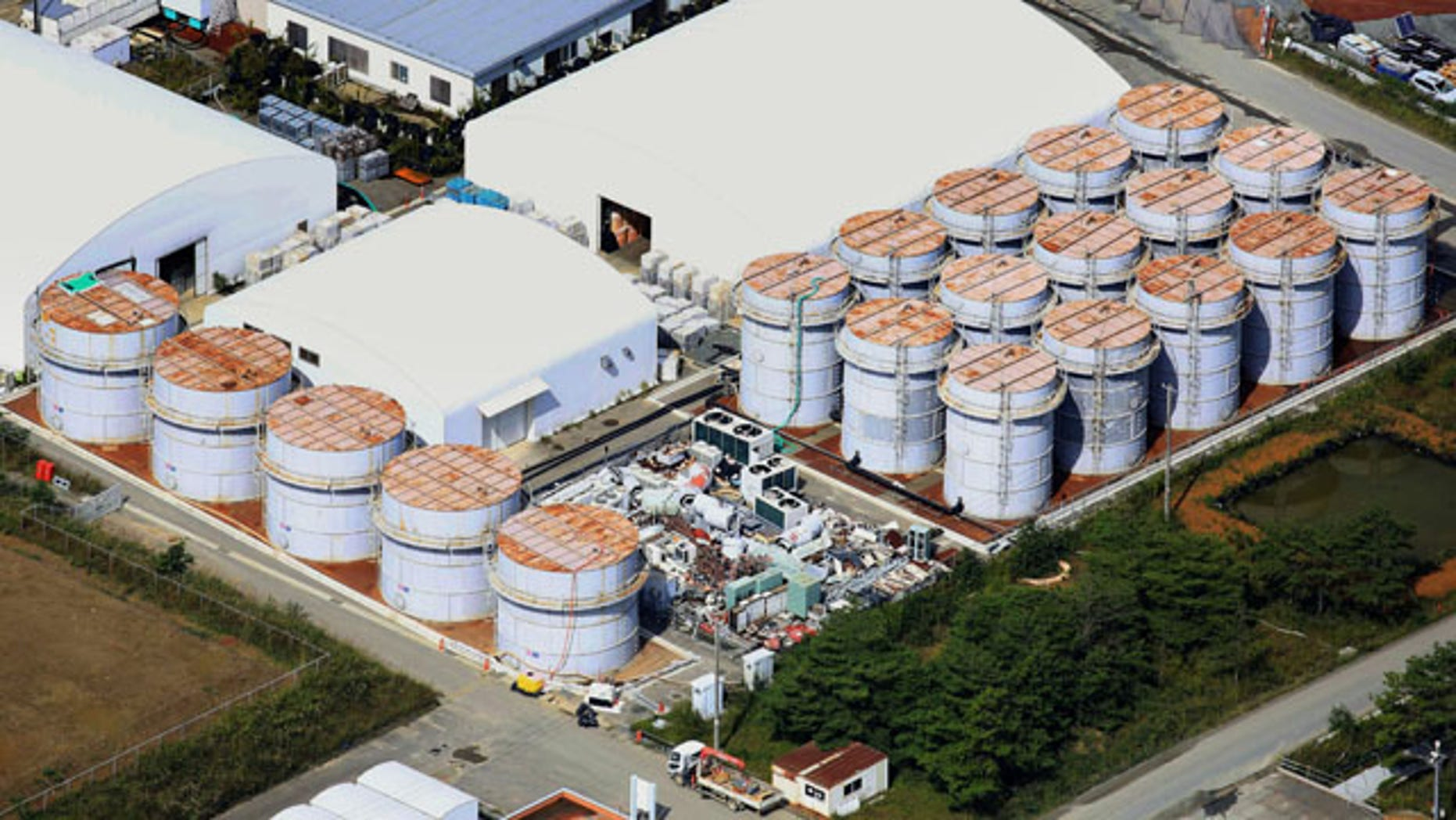 October 3, 2013: This aerial photo shows the storage tank, fifth from left at left plot, which workers detected the water dripping from the top, at the Fukushima Dai-ichi nuclear plant at Okuma town in Fukushima prefecture. (AP Photo)