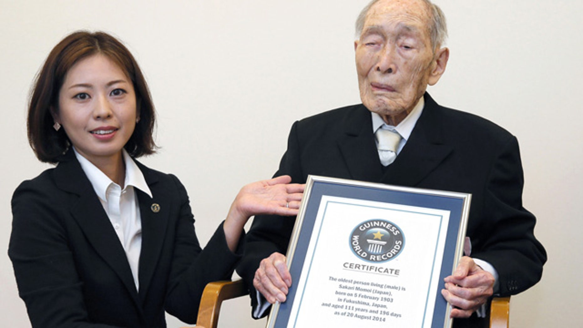 August 20, 2014: Sakari Momoi, a 111-year-old Japanese retired educator, poses for a photo after receiving a certificate from a Guinness World Records official, left, in Tokyo. Momoi was recognized as the worlds oldest living man on Wednesday, succeeding Alexander Imich of New York, who died in April at the age of 111 years, 164 days. (AP Photo/Kyodo News)