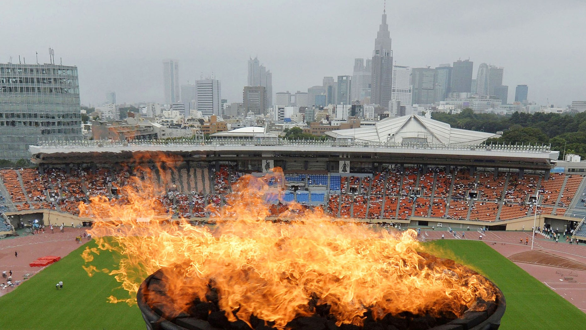 A flame is ignited at the Olympic cauldron at National Stadium in Tokyo to celebrate the city's successful bid to host the 2020 Olympics, Sunday, Sept. 8, 2013.  (AP Photo/Kyodo News)