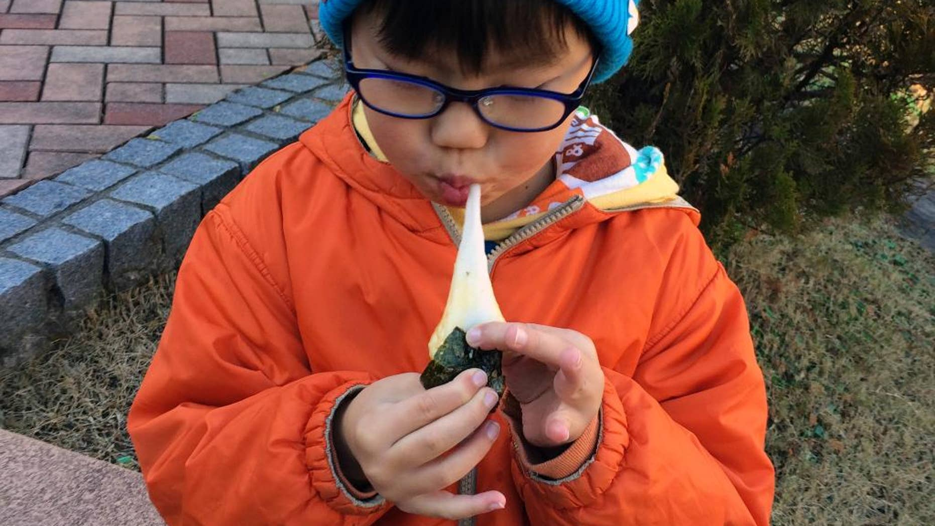 """In this Saturday, Dec. 13, 2014 photo, a boy eats a freshly pounded rice cake, or """"mochi,"""" wrapped in a sheet of seasoned laver, or """"nori,"""" at a park during a rice pounding gathering, part of the annual preparation for the New Year's celebration at a park in Yokohama, near Tokyo. At least nine people have reportedly choked to death on New Year's rice cakes in Japan, and officials are urging people to chew slowly on the treats. (AP Photo/Tetsuya Saruta)"""