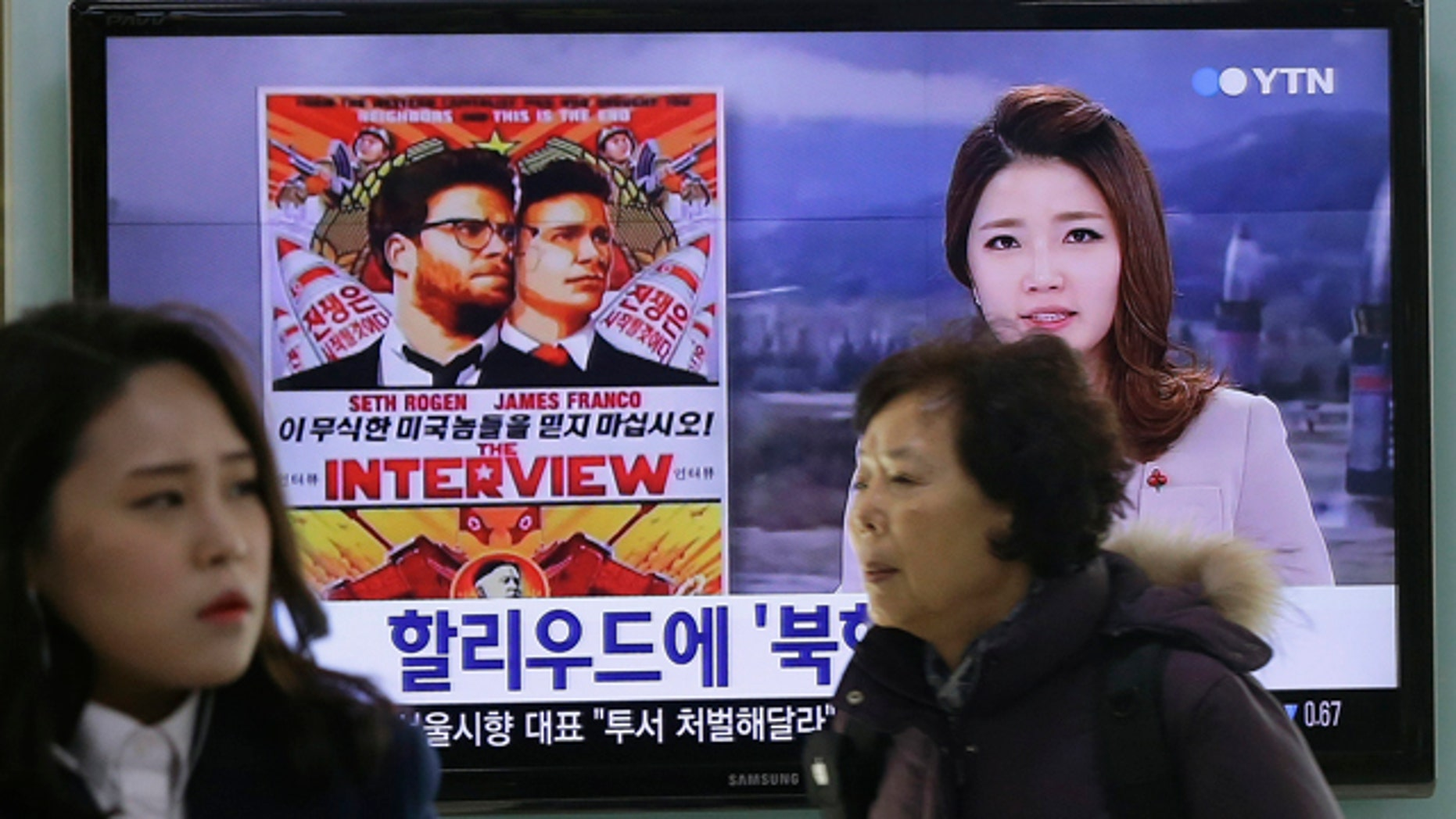 FILE - In this Dec. 22, 2014 file photo, people walk past a TV screen showing a poster of Sony Pictures Entertainment's 'The Interview' in a news report at the Seoul Railway Station in Seoul, South Korea. (AP Photo/Ahn Young-joon, File)