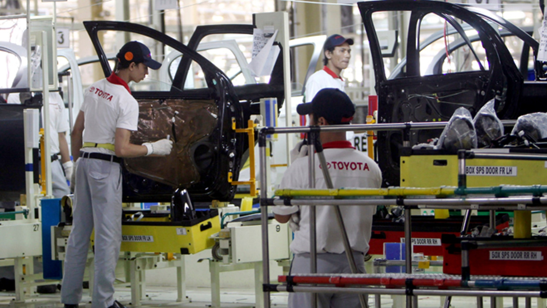 FILE - In this March 15, 2013 file photo, Indonesian workers assemble passenger cars at the new Toyota plant in Karawang, West Java, Indonesia after Toyota officially opened their second manufacturing plant in the country. Toyota is building two new auto plants, one in Mexico and the other in China, ending a three-year hiatus from such ambitions that the Japanese automaker voluntarily imposed on itself after a massive recall scandal. Toyota Motor Corp. announced Wednesday, April 15, 2015 it will invest $1 billion for the plant in Guanajuato, Mexico, creating 2,000 jobs, to make the Corolla subcompact - one of Toyotaâs biggest hits. (AP Photo/Tatan Syuflana, File)