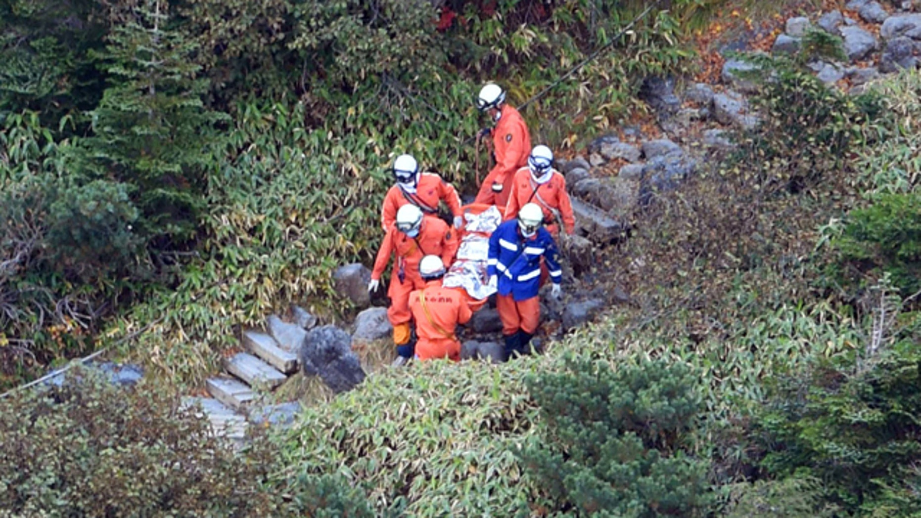 October 1, 2014: Rescuers carry a person found on Mount Ontake in central Japan. Search efforts for people missing since Saturday's surprise eruption resumed Wednesday morning. (AP Photo/Kyodo News)