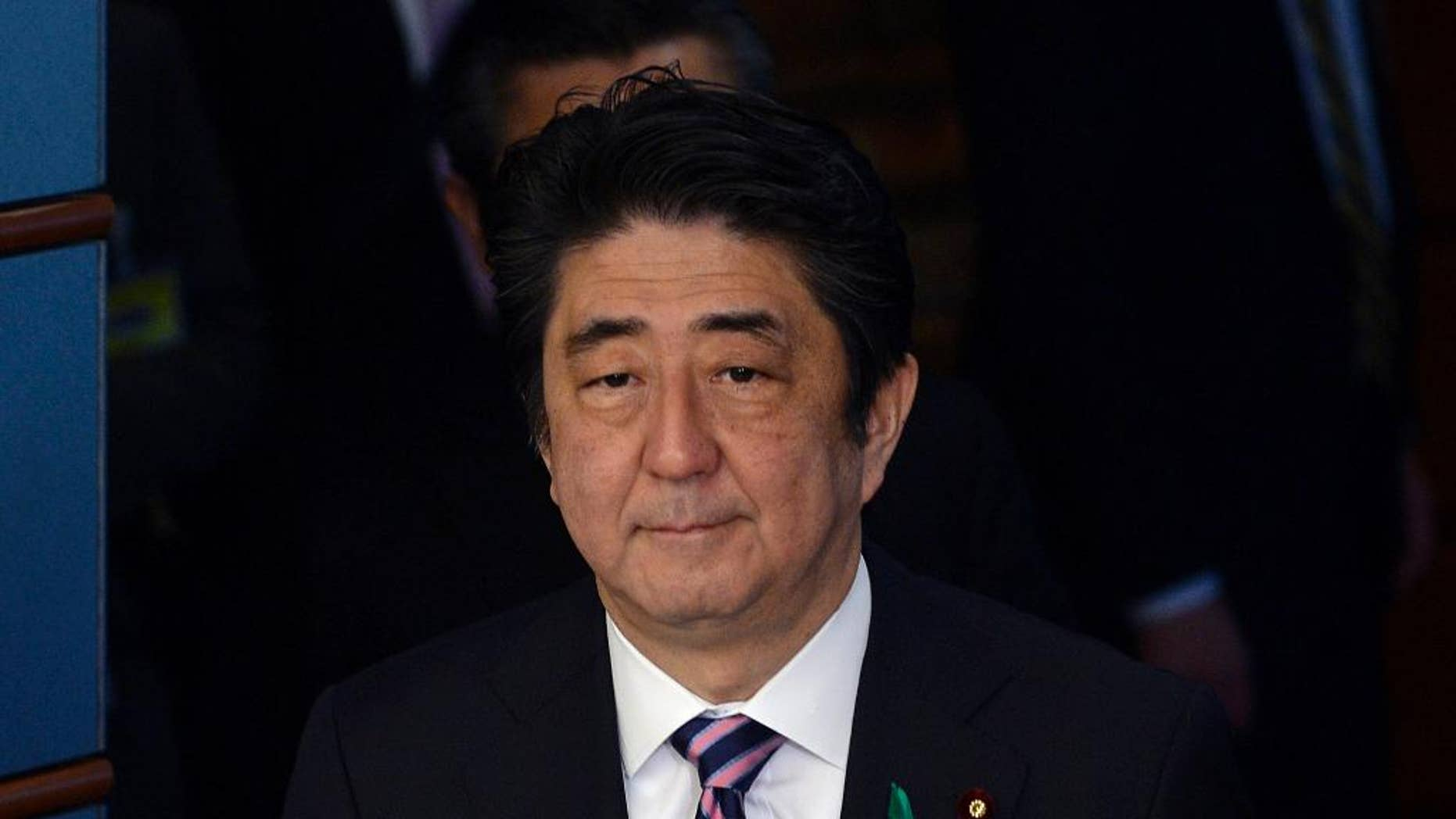 Japanese Prime Minister Shinzo Abe walks on his way to meet a delegation of US representatives at the premier's official residence in Tokyo, Japan, Monday, April 21, 2014. Japan's Prime Minister Abe has sent a religious offering to a Tokyo shrine that honors the dead including executed war criminals, a center of tension with Japan's neighbors. Abe's offering Monday at the Yasukuni Shrine marks the April 21-23 spring festival, one of the shrine's key annual events. But the move suggests he will not visit Yasukuni ahead of President Barack Obama's visit beginning Wednesday. (AP Photo/Franck Robicon, Pool)