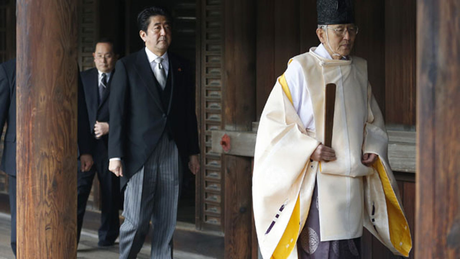 """December 26, 2013: Japanese Prime Minister Shinzo Abe, second from right, follows a Shinto priest to pay respect for the war dead at Yasukuni Shrine in Tokyo. The visit to the shrine, which honors 2.5 million war dead including convicted class A war criminals, appears to be a departure from Abe's """"pragmatic"""" approach to foreign policy, in which he tried to avoid alienating neighboring countries. (AP)"""