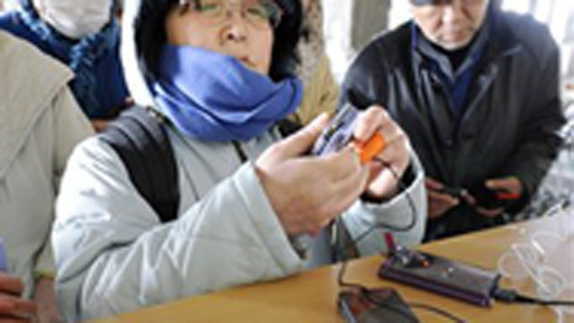 People recharge their cell phones at a shelter for Friday's earthquake and tsunami victims in Ishinomaki, Miyagi Prefecture, northern Japan, Thursday, March 17, 2011.