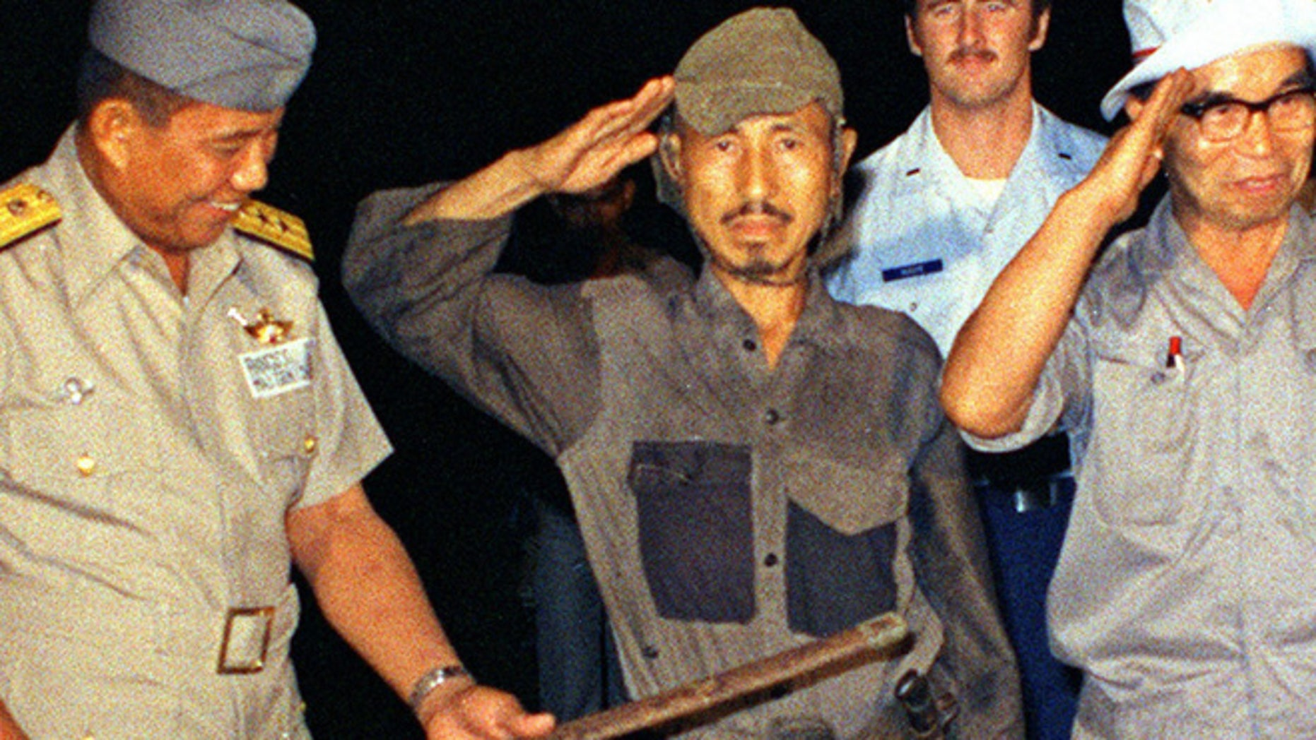 FILE 1974: Hiroo Onoda, center, salutes after handing over his military sword on Lubang Island, Philippines, when he comes out of hiding in the jungle.