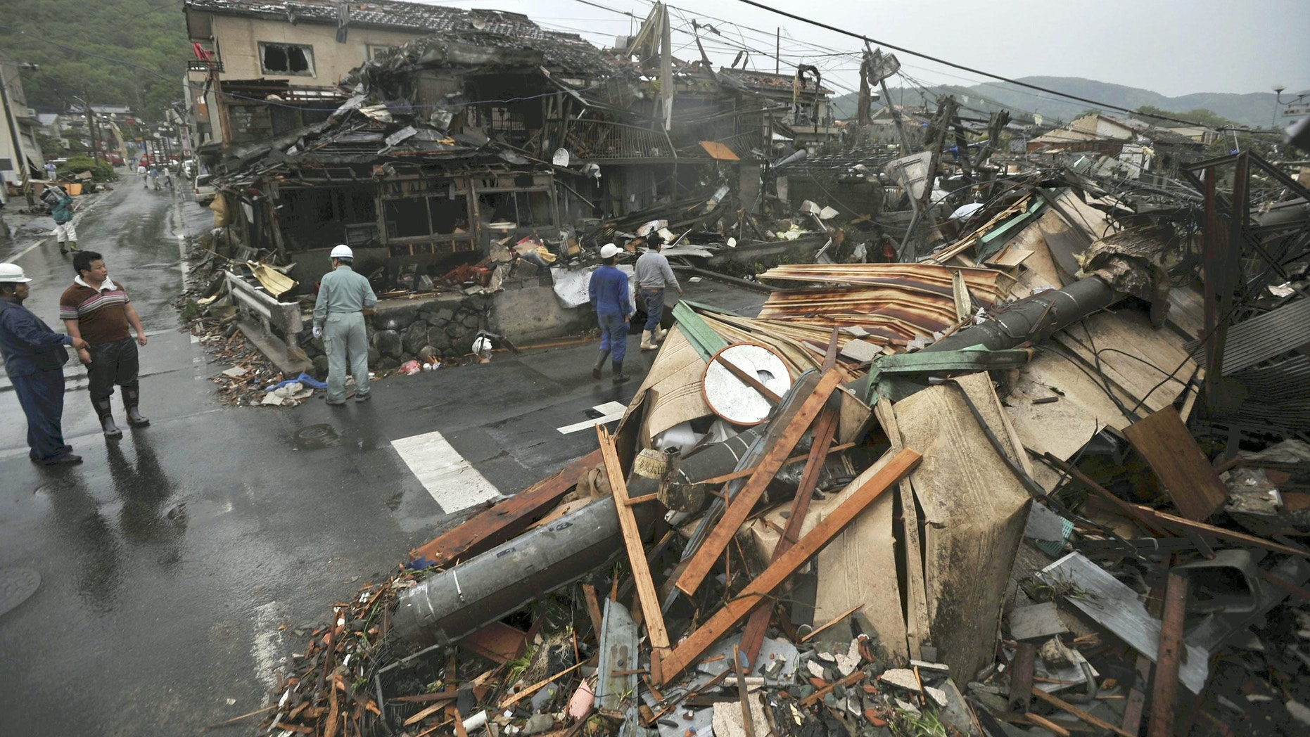 May 6, 2012: People look at damaged buildings after a tornado struck Tsukuba city, northeast of Tokyo.