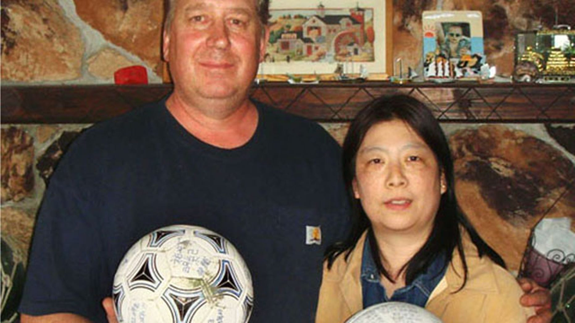 April 21, 2012: David and Yumi Baxter hold a soccer ball and a volleyball which David found, at their house in the suburbs of Anchorage, Alaska