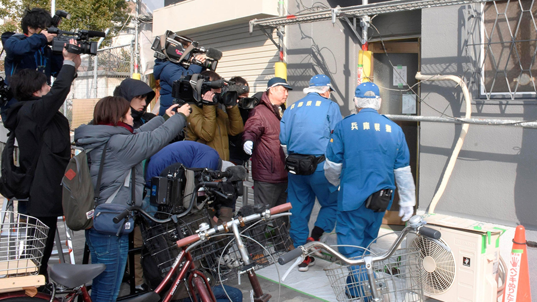 Hyogo Prefectural authorities enter a lodging facility where the severed head of a woman was found, after an American man was arrested on suspicion of confining the missing 27-year-old woman.