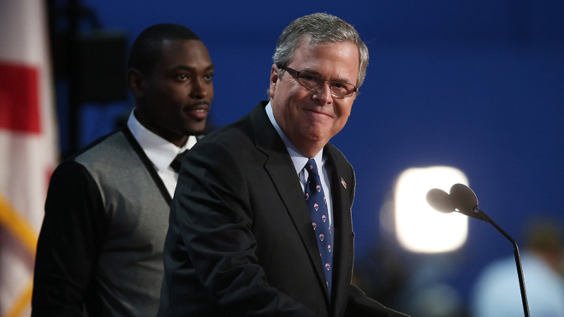 TAMPA, FL - AUGUST 30:  Former Florida Gov. Jeb Bush speaks on stage with student Frantz Placide (L) of Miami, FL during the final day of the Republican National Convention at the Tampa Bay Times Forum on August 30, 2012 in Tampa, Florida. Former Massachusetts Gov. Mitt Romney was nominated as the Republican presidential candidate during the RNC which will conclude today.  (Photo by Win McNamee/Getty Images)