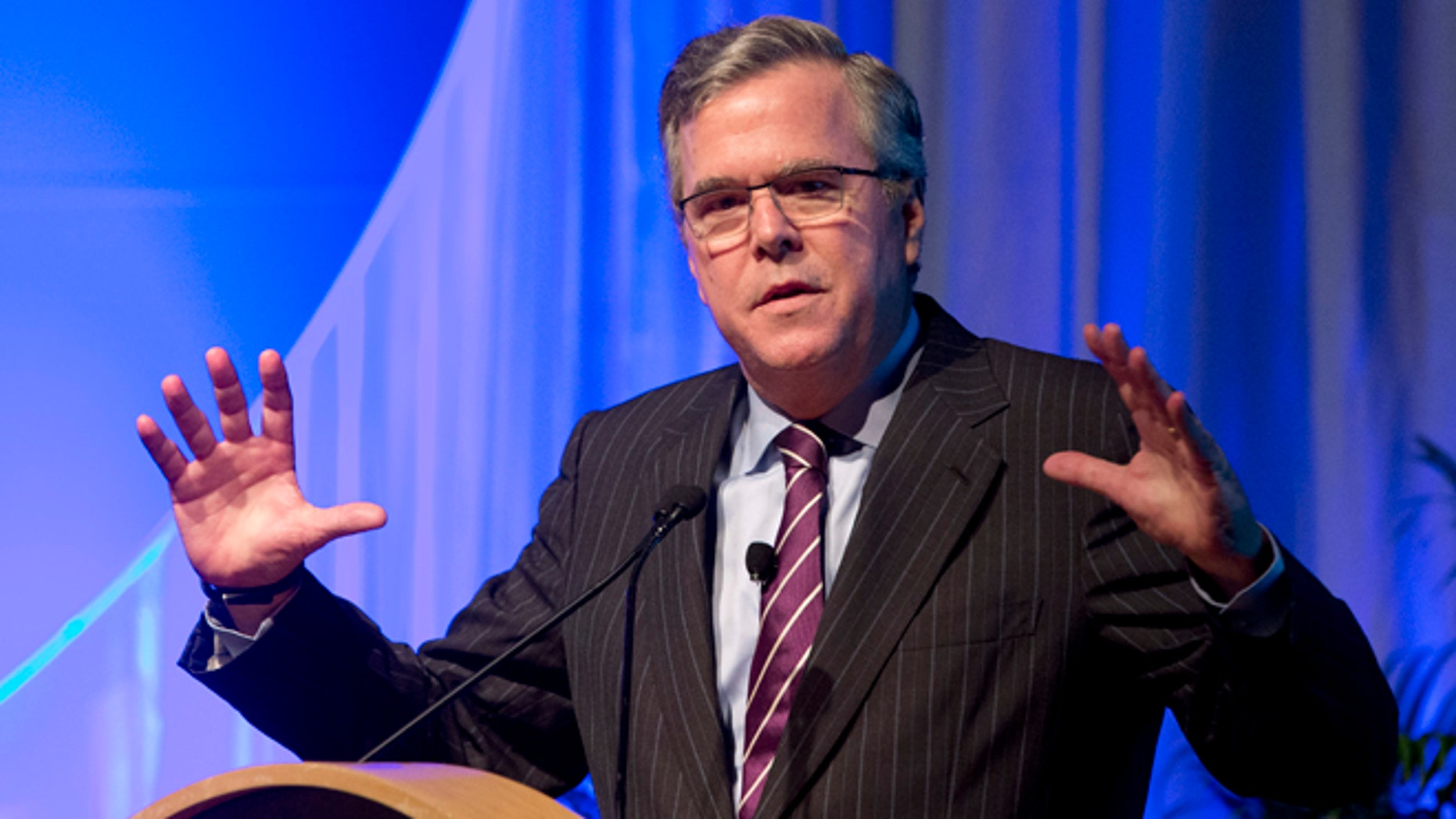 """This Jan. 29, 2014 photo, former Florida Gov. Jeb Bush gestures as he speaks at the Inside ITFs Conference at the Westin Diplomat Resort & Spa in Hollywood, Fla.  Bush says he's all the speculation about whether he'll run for president in 2016 is actually getting him more attention than if he had already entered the race. The former Republican governor of Florida says that's not by design, and that he'll make his decision before year's end. He tells Fox News Channel that the state of politics is ``crazy right now."""" (AP Photo/Wilfredo Lee)"""