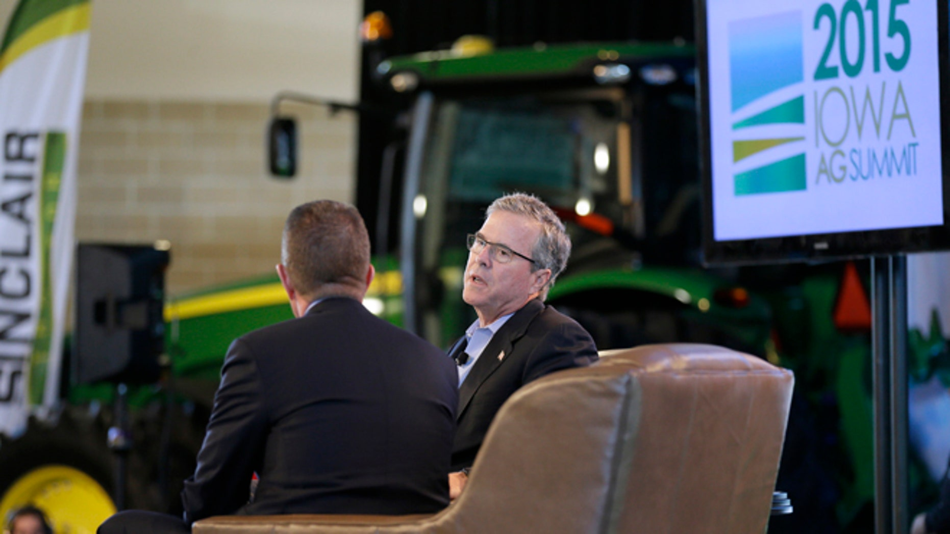 In this March 7, 2015, photo, former Florida Gov. Jeb Bush is interviewed by host Bruce Rastetter, left, during the Iowa Agriculture Summit in Des Moines, Iowa. After a flurry of fundraising, formal speeches about economics and global affairs Bush got down to business this weekend appearing at the Pizza Ranch in Cedar Rapids, Iowa, after a stop at the Agricultural Summit. (AP Photo/Charlie Neibergall)