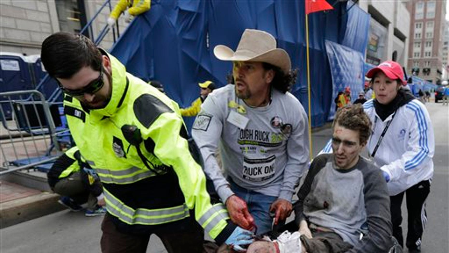 April 15: An emergency responder and volunteers, including Carlos Arredondo, in the cowboy hat, push Jeff Bauman in a wheel chair after he was injured in an explosion near the finish line of the Boston Marathon.
