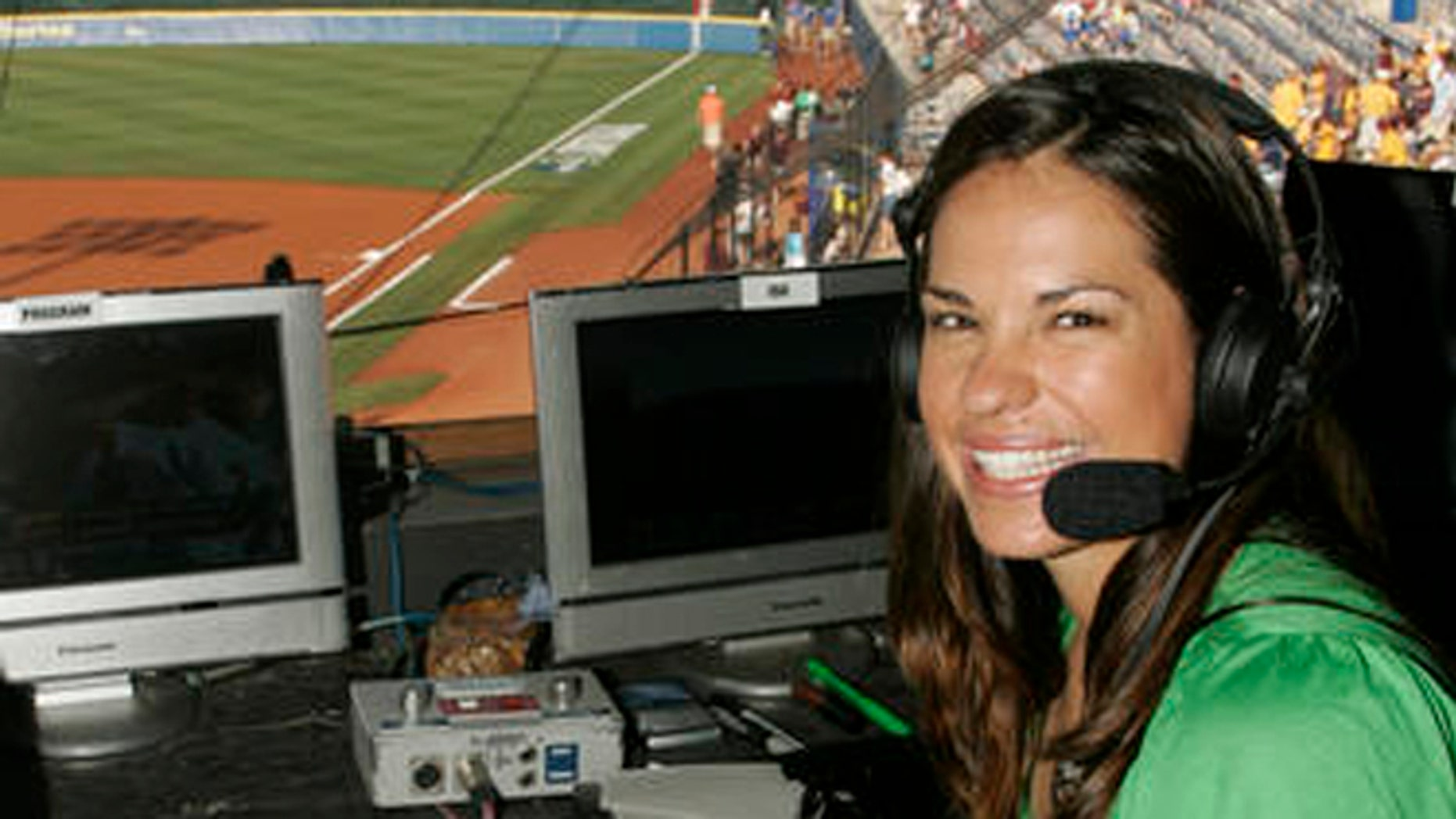 """FILE - In this May 29, 2009 file photo, USA softball player Jessica Mendoza poses for a photo in the ESPN broadcast booth at the Women's College World Series in Oklahoma City.  Mendoza chatted up Kyle Schwarber, broke down pitcher's tendencies and dealt with social media criticism in her historic first full season covering baseball for ESPN. Mendoza recently shuttled between Cleveland and Chicago, giving World Series updates eight times a day for """"Baseball Tonight"""" and """"Sports Center.""""(AP Photo)"""