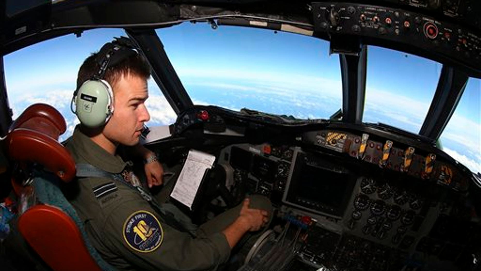 """In this Wednesday, March 26, 2014 photo, Flight Lt. Russell Adams looks out from the cockpit on board a Royal Australian Air Force AP-3C Orion, during a search for the missing Malaysia Airlines Flight 370 in the southern Indian Ocean. A French satellite scanning the Indian Ocean for remnants of the missing jetliner found a possible plane debris field containing 122 objects, a top Malaysian official said Wednesday, calling it """"the most credible lead that we have."""" (AP Photo/Paul Kane, Pool)"""