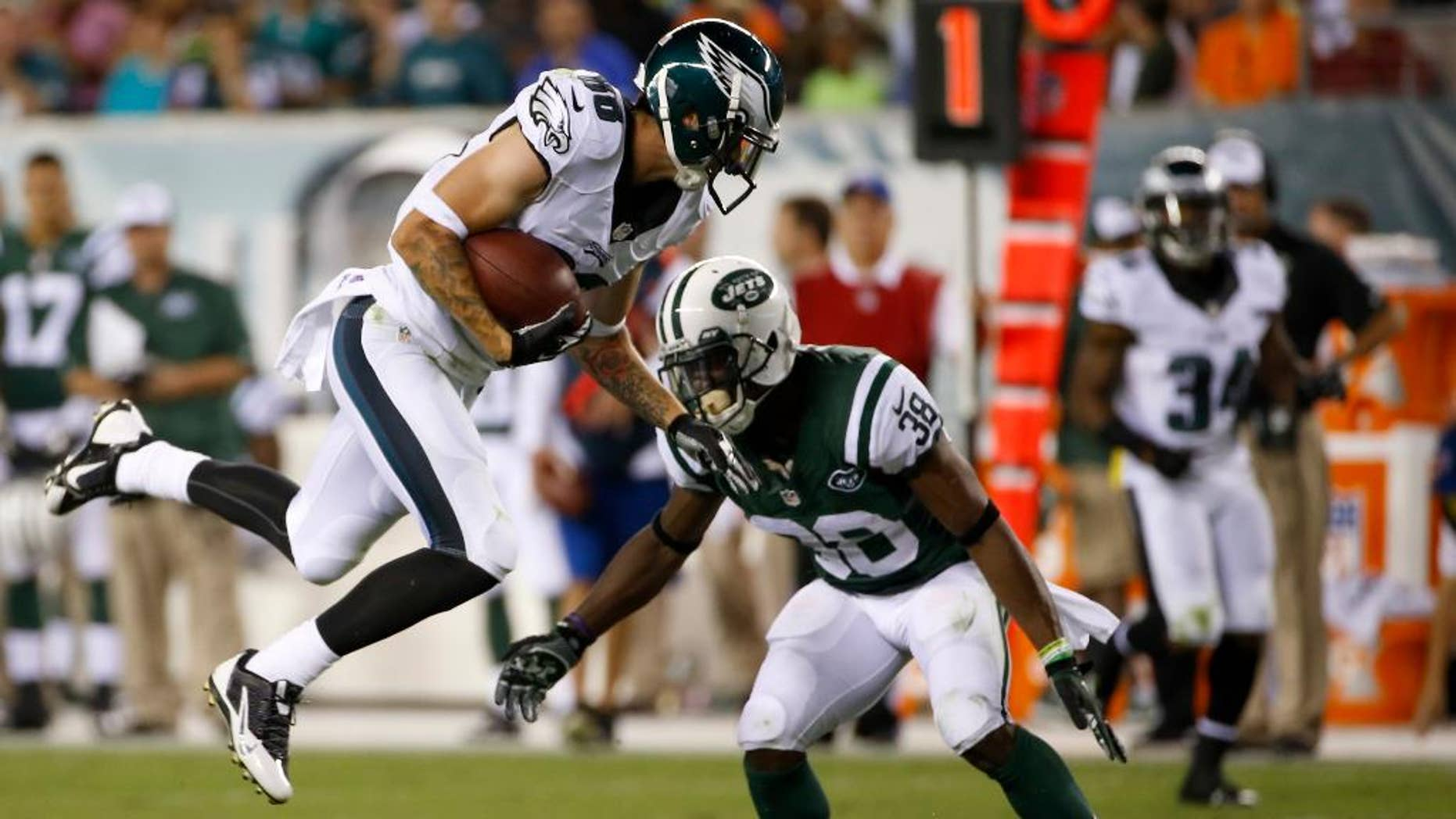 Philadelphia Eagles' Jeff Maehl, left, tries to leap past New York Jets' LeQuan Lewis after catching a pass during the first half of an NFL preseason football game, Thursday, Aug. 28, 2014, in Philadelphia. (AP Photo/Michael Perez)
