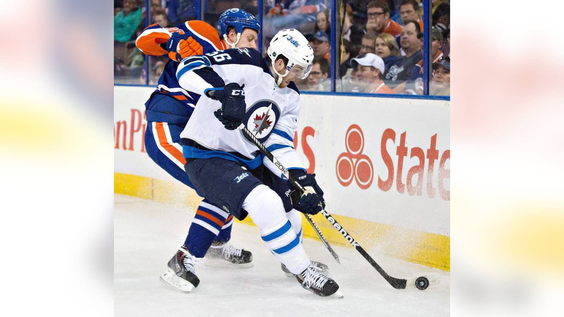 Edmonton Oilers goalie Viktor Fasth (35) and Mark Fayne (5) celebrate a win over the Winnipeg Jets during an NHL hockey game in Edmonton, Alberta, on Monday, Sept. 29, 2014. (AP Photo/The Canadian Press, Jason Franson)