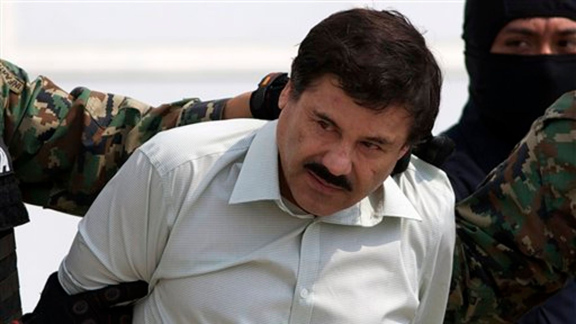 """Joaquin """"El Chapo"""" Guzman is escorted to a helicopter in handcuffs by Mexican navy marines at a navy hanger in Mexico City, Saturday, Feb. 22, 2014. A senior U.S. law enforcement official said Saturday, that Guzman, the head of Mexicoís Sinaloa Cartel, was captured alive overnight in the beach resort town of Mazatlan. Guzman faces multiple federal drug trafficking indictments in the U.S. and is on the Drug Enforcement Administrationís most-wanted list. (AP Photo/Eduardo Verdugo)"""