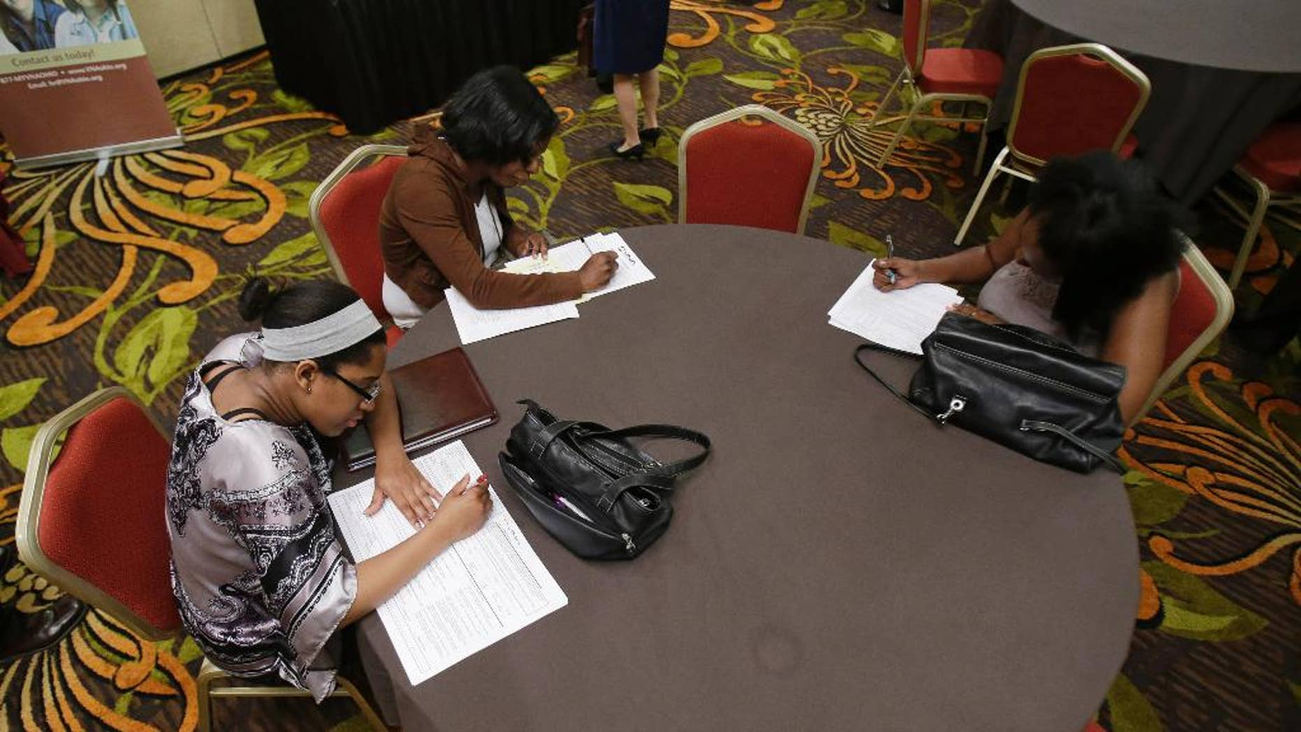 In this Thursday, June 12, 2014 photo, Desirae Gooch, left, fills out an application for a nurse's assistant job, alongside other job seekers filling out applications at the Cleveland Career Fair in Independence, Ohio. The Labor Department issues its May report on job openings and labor turnover on Tuesday, July 8, 2014. (AP Photo/Tony Dejak)