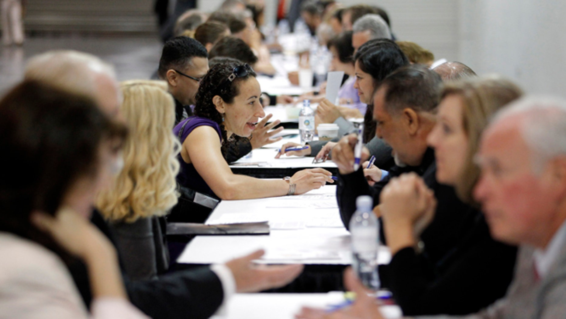 June 13, 2012: Job seekers have their resumes reviewed at a job fair expo in Anaheim, Calif.