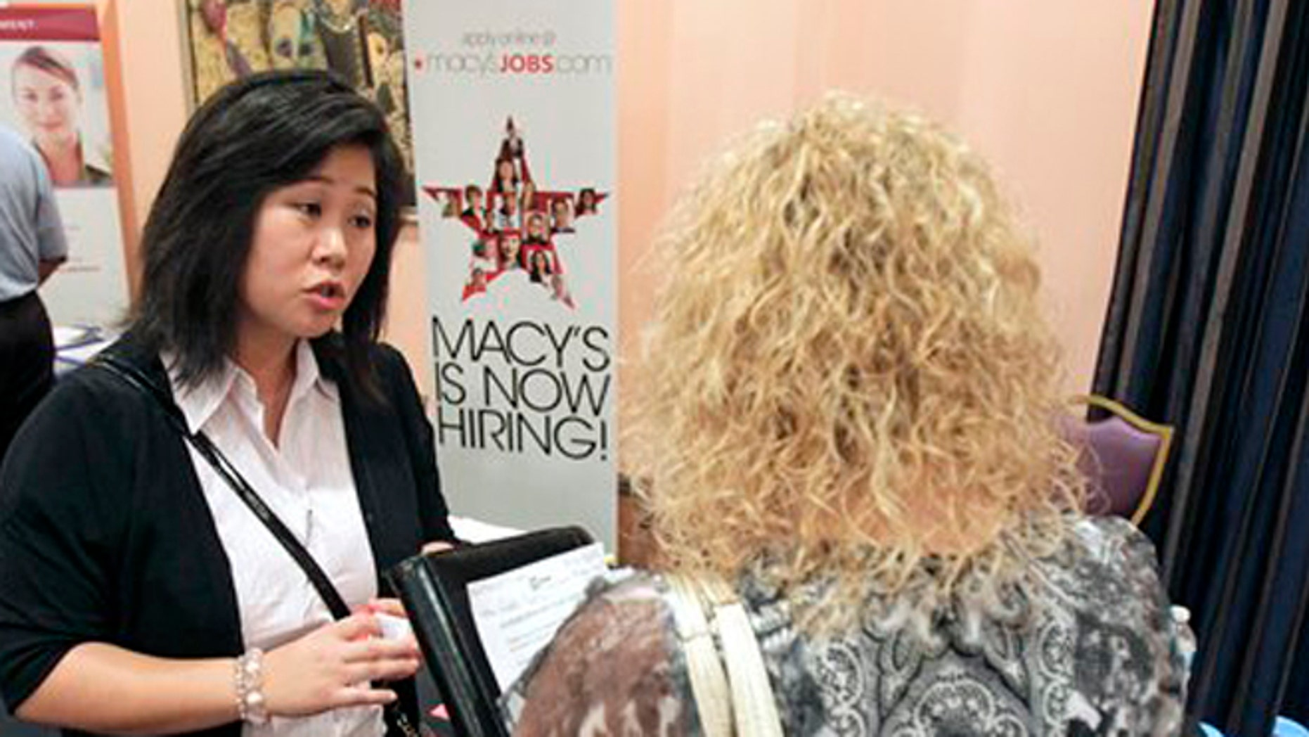 May 30, 2012:  Mi-Ran Park-Wong, of Macy's, speaks to a job applicant during a career expo sponsored by Jobs Direct USA in Orlando, Fla.