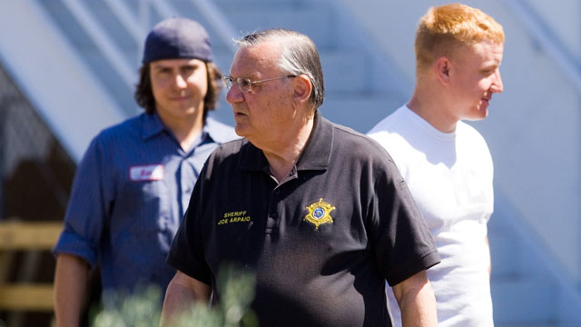 May 6: Maricopa County Sheriff Joe Arpaio talks with workers after an immigration raid on a business in west Phoenix.