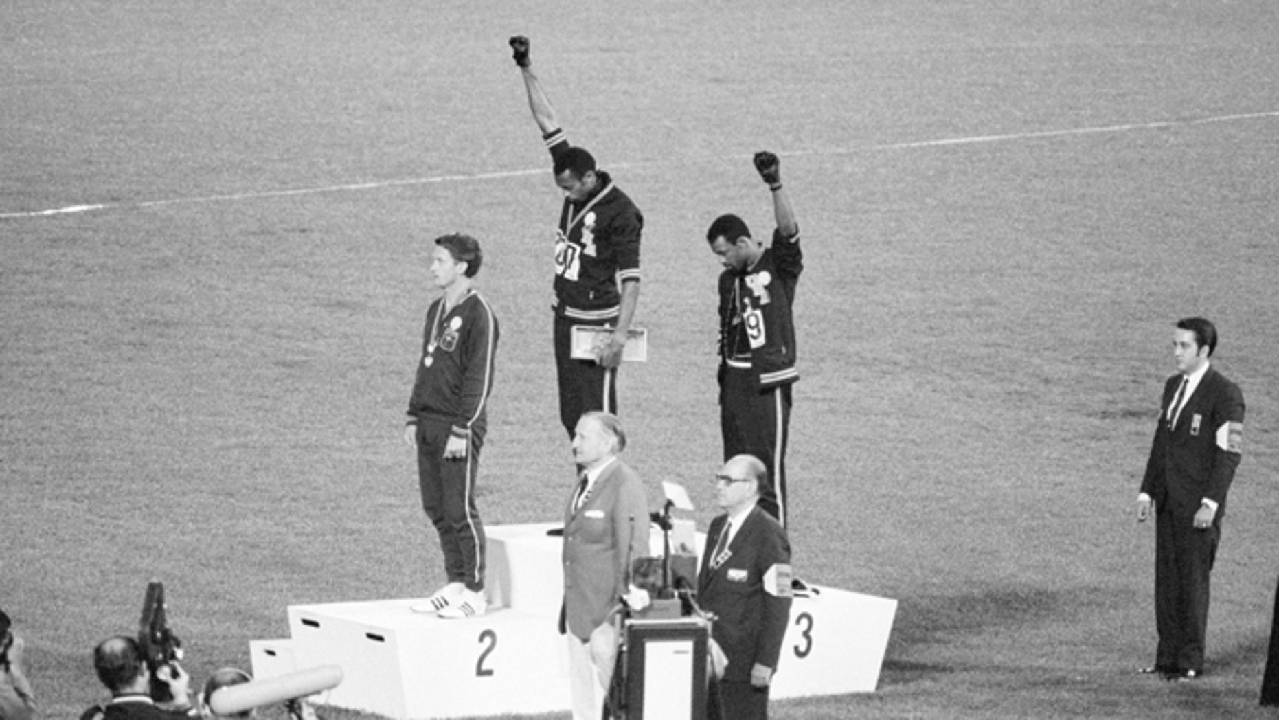 Tommie Smith and John Carlos, gold and bronze medalists in the 200-meter run at the 1968 Olympic Games, engage in a victory stand protest against unfair treatment of blacks in the United States. With heads lowered and black-gloved fists raised in the black power salute, they refuse to recognize the American flag and national anthem. Australian Peter Norman is the silver medalist.