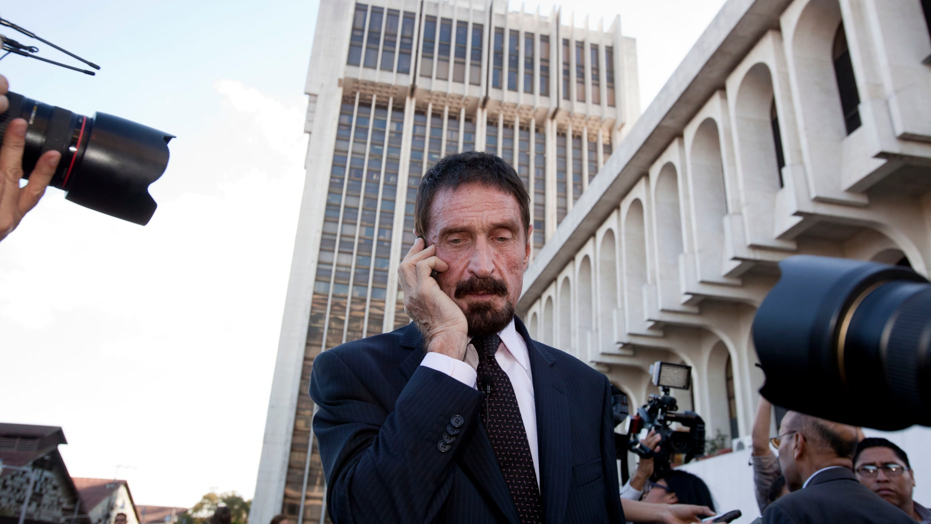 Dec. 4, 2012: Software company founder John McAfee talks on his mobile phone after a press conference outside the Supreme Court in Guatemala City.
