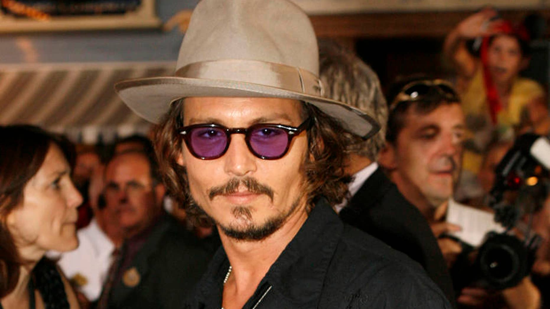 """Actor Johnny Depp poses for photographers at the film premiere of  """"Pirates of the Caribbean: Dead Man's Chest,"""" at the Disneyland theme park in Anaheim, Calif., on Saturday, June 24, 2006. (AP Photo/Matt Sayles)"""