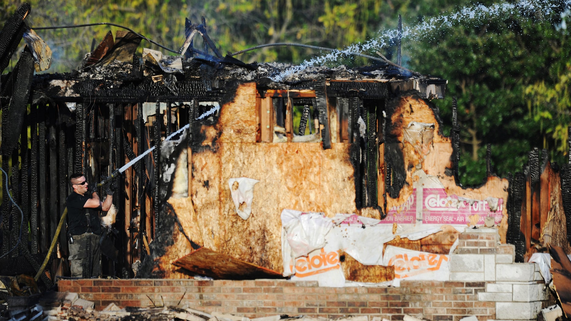 Aug. 6, 2012-  A Carl Junction, Missouri firefighter works to extinguish the smoldering remains of the Islamic Society of Joplin mosque.