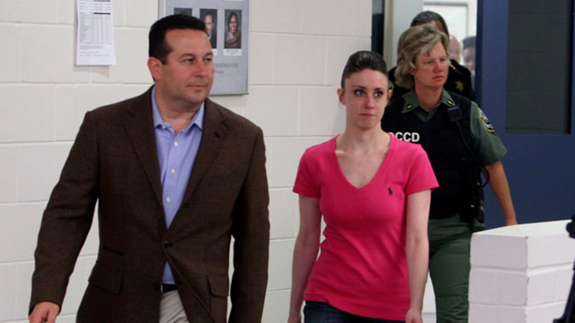 Casey Anthony, center, walks out of the Orange County Jail with her attorney Jose Baez, left,  during her release in Orlando, Fla., early Sunday, July 17, 2011.