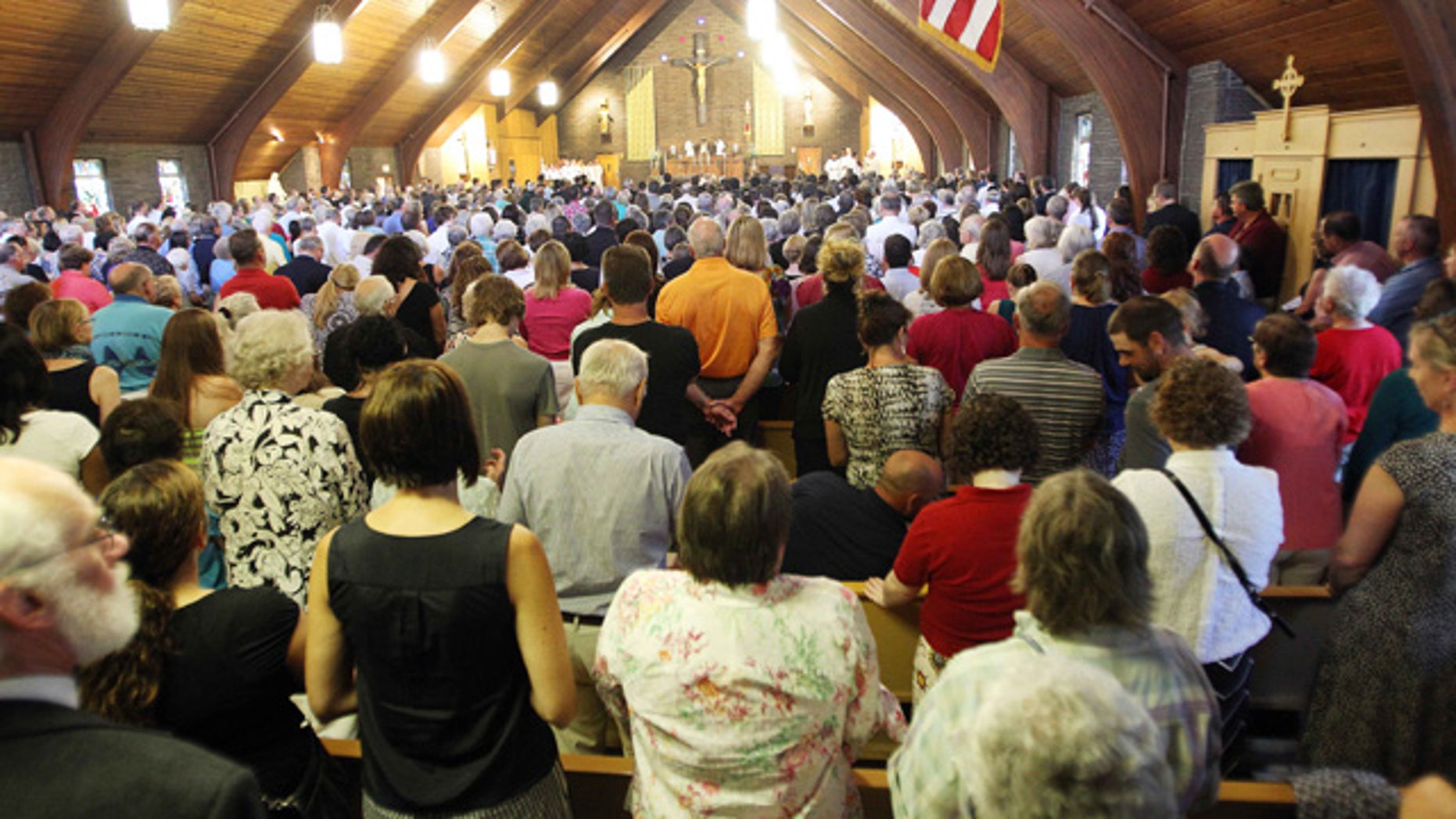 August 24, 2014: Mourners pack Our Lady of the Holy Rosary Catholic church during a special Mass for murdered journalist James Foley in his hometown of Rochester, N.H. (AP Photo/Jim Cole)