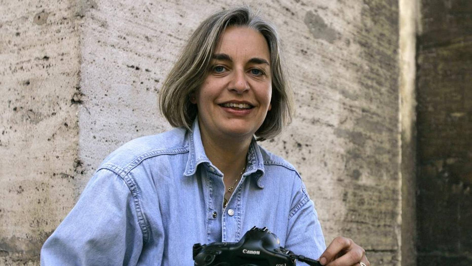 FILE - In this April 7, 2005 file photo, Associated Press photographer Anja Niedringhaus poses in Rome. Niedringhaus, 48, was killed and an AP reporter was wounded on April 4, 2014, when an Afghan policeman opened fire while they were sitting in their car in eastern Afghanistan. At least 60 journalists around the world were killed in 2014 while on the job or because of their work, and 44 percent of them were targeted for murder, the Committee to Protect Journalists says. (AP Photo/Peter Dejong, File)