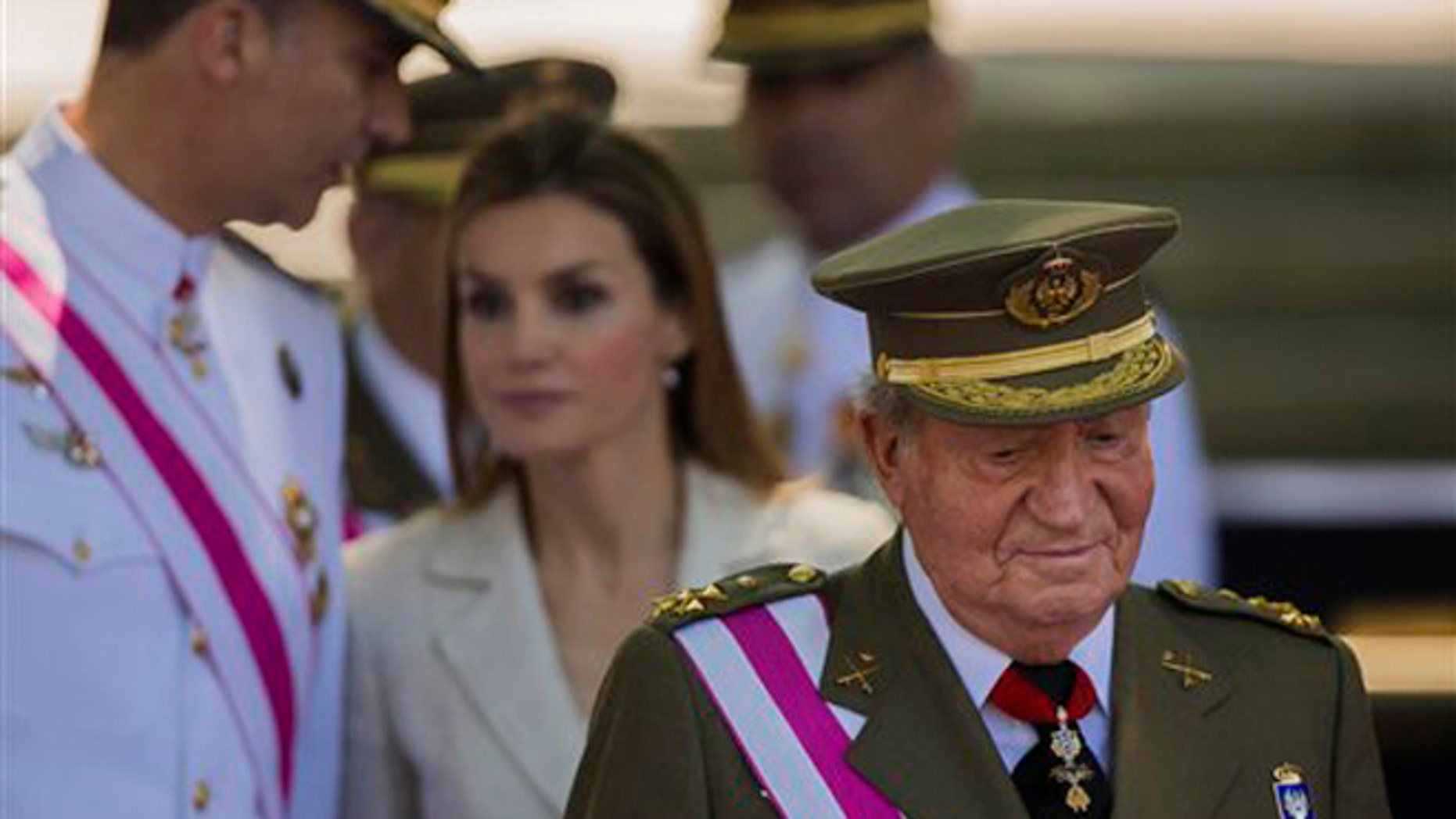 Spanish Crown Prince Felipe, background left, talks with Spanish Princess Letizia, as Spanish King Juan Carlos, foreground looks on, during a military parade on Armed Forces day in Madrid, Spain, Sunday, June 8, 2014. King Juan Carlos plans to abdicate and pave the way for his son, Crown Prince Felipe, to become the country's next king. The 76-year-old Juan Carlos oversaw his country's transition from dictatorship to democracy but has had repeated health problems in recent years. His popularity also dipped following royal scandals, including an elephant-shooting trip he took in the middle of Spain's financial crisis that tarnished the monarch's image. The king came to power in 1975, two days after the death of longtime dictator Francisco Franco. (AP Photo/Andres Kudacki)