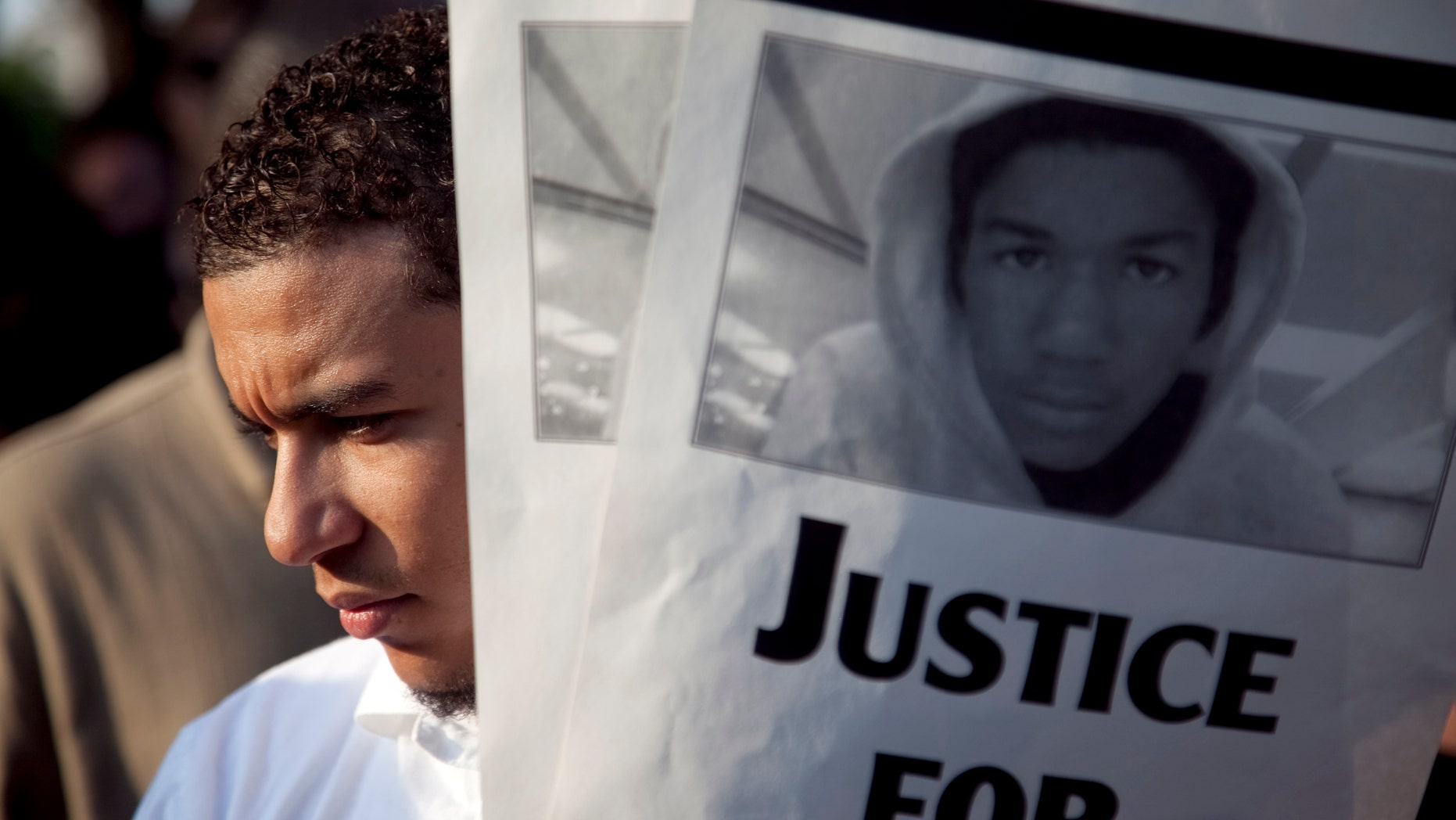 A protestor holds flyers during a rally outside the Texas State Capitol in Austin on Tuesday depicting Travyon Martin, the unarmed Florida teen killed last month.  The case has become a racial flashpoint that has civil rights leaders and others leading  protests in Florida and around the country. (AP Photo/Thomas Allison, Daily Texan)
