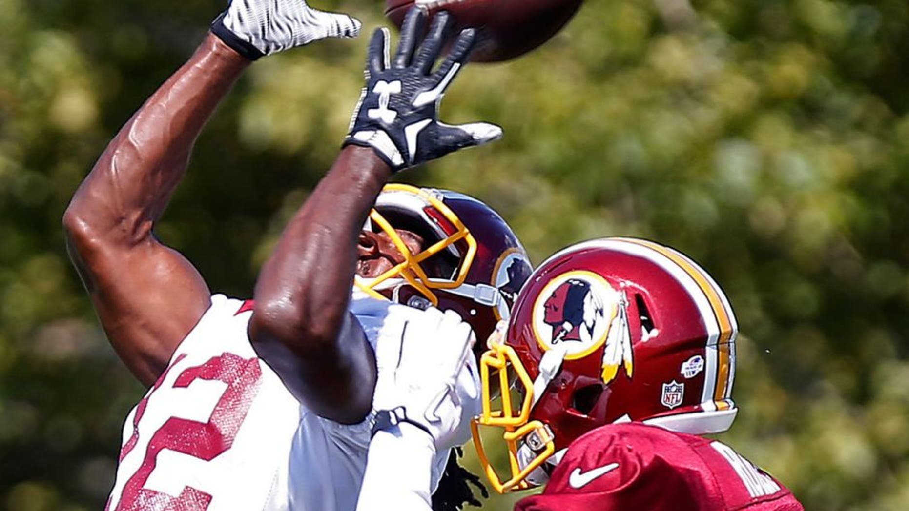 Aug 1, 2015; Richmond, VA, USA; Washington Redskins wide receiver Andre Roberts (12) catches the ball as defensive back Justin Rogers (25) defends during afternoon practice as part of day three of training camp at Bon Secours Washington Redskins Training Center. Mandatory Credit: Geoff Burke-USA TODAY Sports