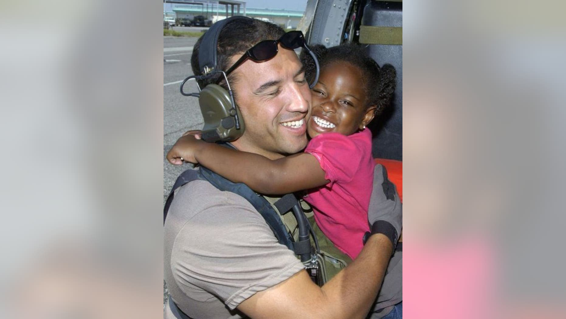 Air Force Reserve Master Sgt. Mike Maroney hugs 3-year-old he rescued in aftermath of Hurricane Katrina in 2005. (Credit: Air Force)