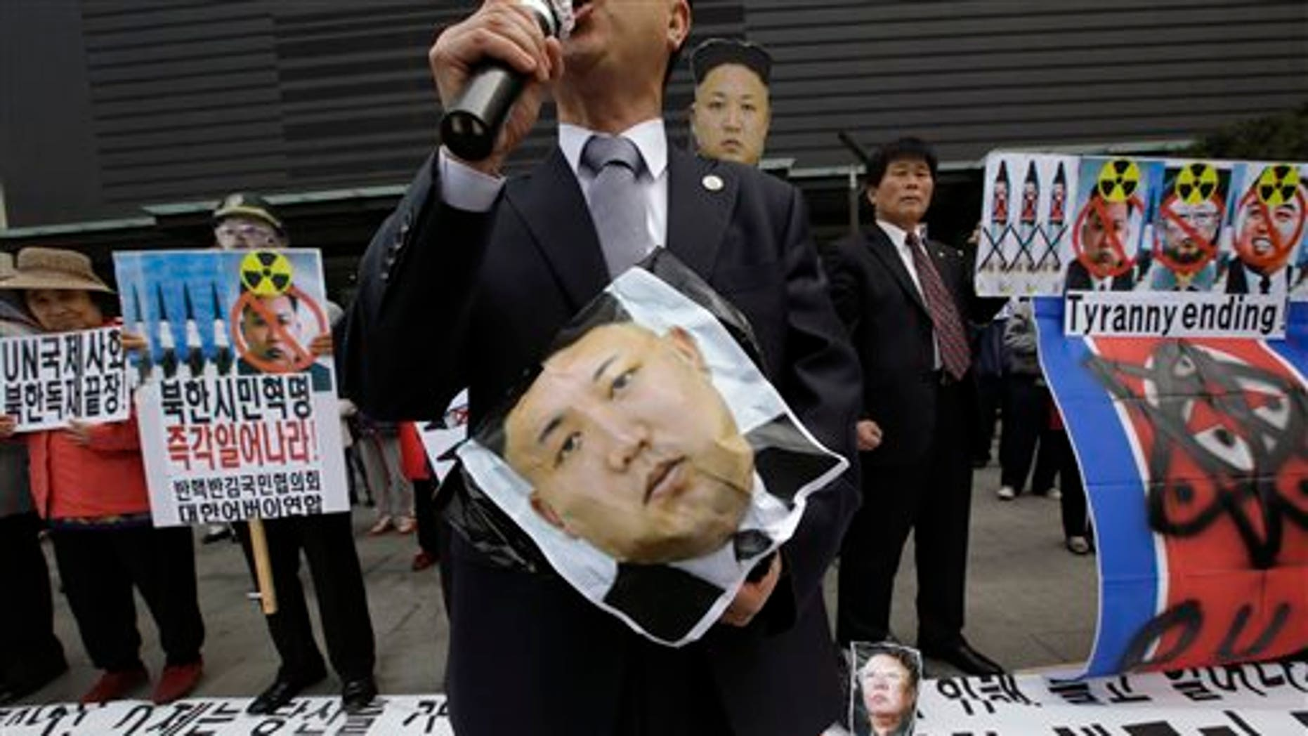 """South Korean protesters hold a picture of North Korean leader Kim Jong Un during an anti-North Korea rally against recent missile launches and provocative acts, on the birthday of its founder, Kim Il Sung, in Seoul, South Korea, Tuesday, April 15, 2014. The banners read: """"Denounce North Korea's dictatorship."""" (AP Photo/Lee Jin-man)"""