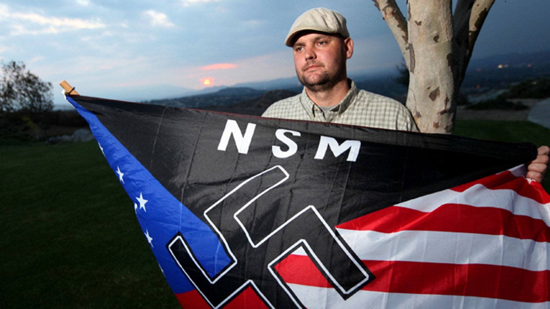 Oct. 22, 2010: Jeff Hall, who was killed by his son, holds a Neo Nazi flag while standing at Sycamore Highlands Park near his home in Riverside, Calif. (AP)