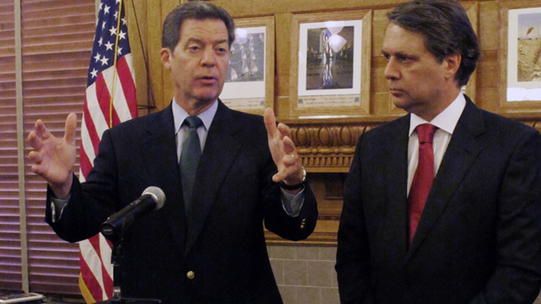 FILE - In this Sept. 11, 2014 file photograph, Kansas Gov. Sam Brownback, left, and Lt. Gov. Jeff Colyer speak at the Statehouse in Topeka. (AP Photo/John Hanna, File)
