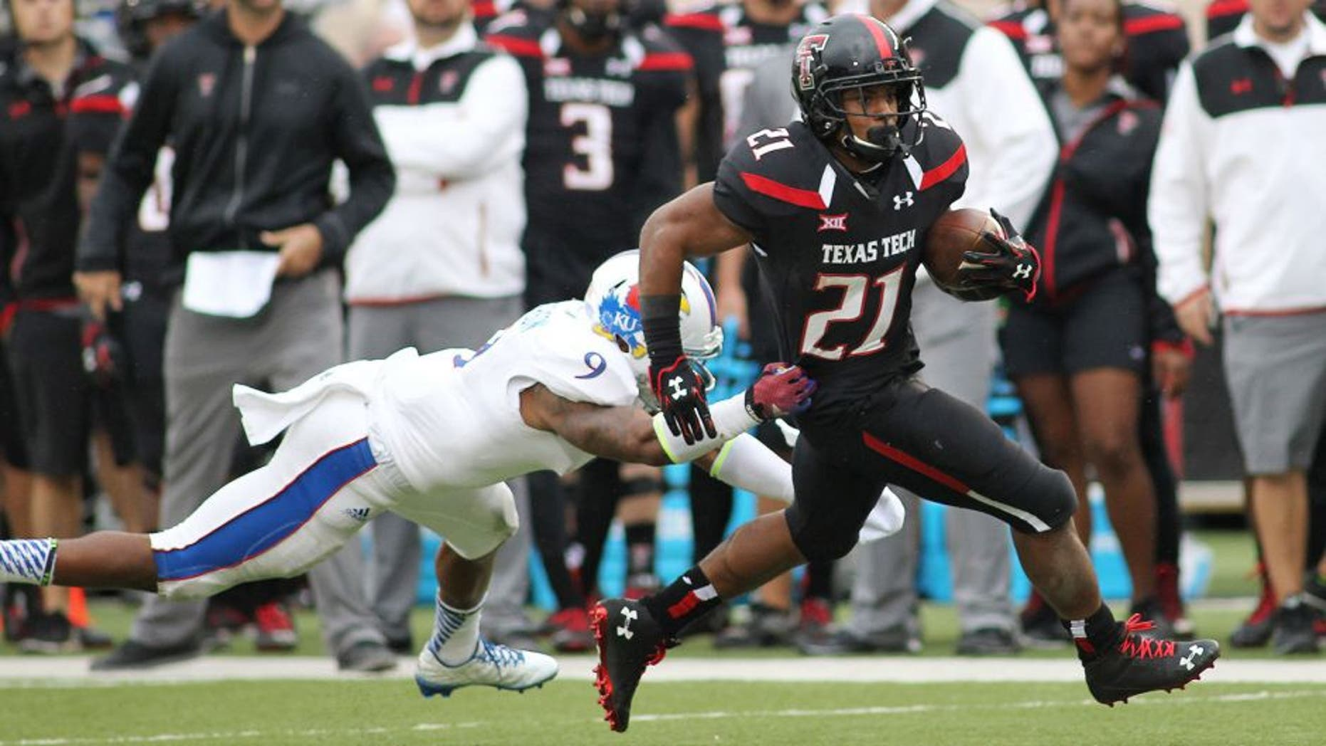 Oct 18, 2014; Lubbock, TX, USA; Kansas Jayhawks safety Fish Smithson (9) attempts to tackle Texas Tech Red Raiders running back DeAndre Washington (21) in the second half at Jones AT&T Stadium. Mandatory Credit: Michael C. Johnson-USA TODAY Sports
