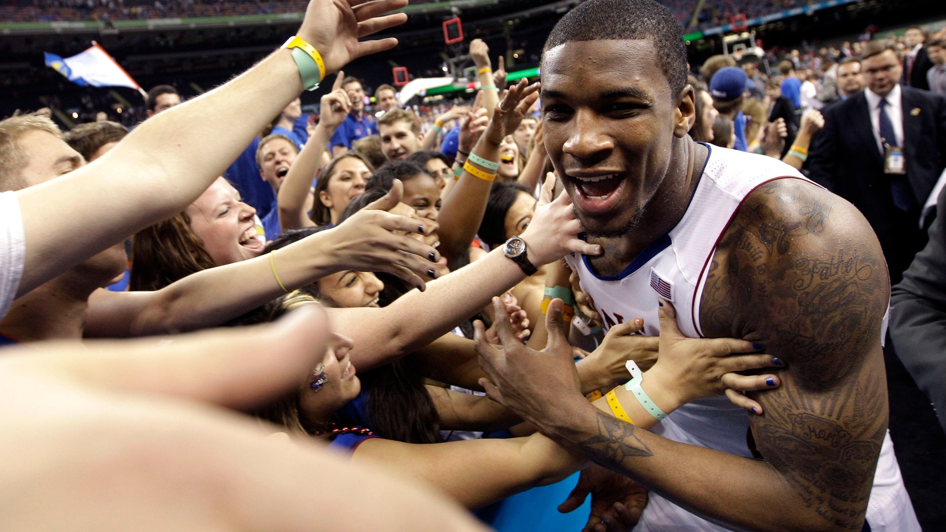Kansas forward Thomas Robinson celebrates with fans after their 64-62 win over Ohio State during an NCAA Final Four semifinal college basketball tournament game Saturday, March 31, 2012, in New Orleans. (AP Photo/David J. Phillip)
