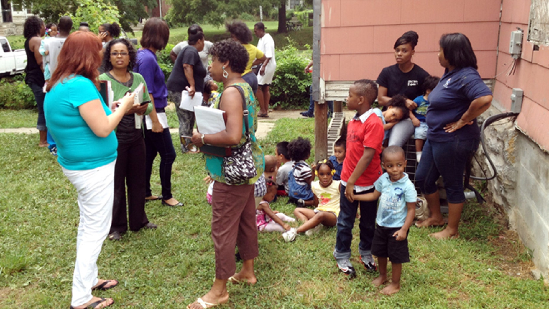 July 30, 2013: Dena Washington, middle of 3 women on left, director of the Christian Academy Child Care, stands behind a house near the center with children waiting to be picked up after a car crashed into the day care in Kansas City, Mo.