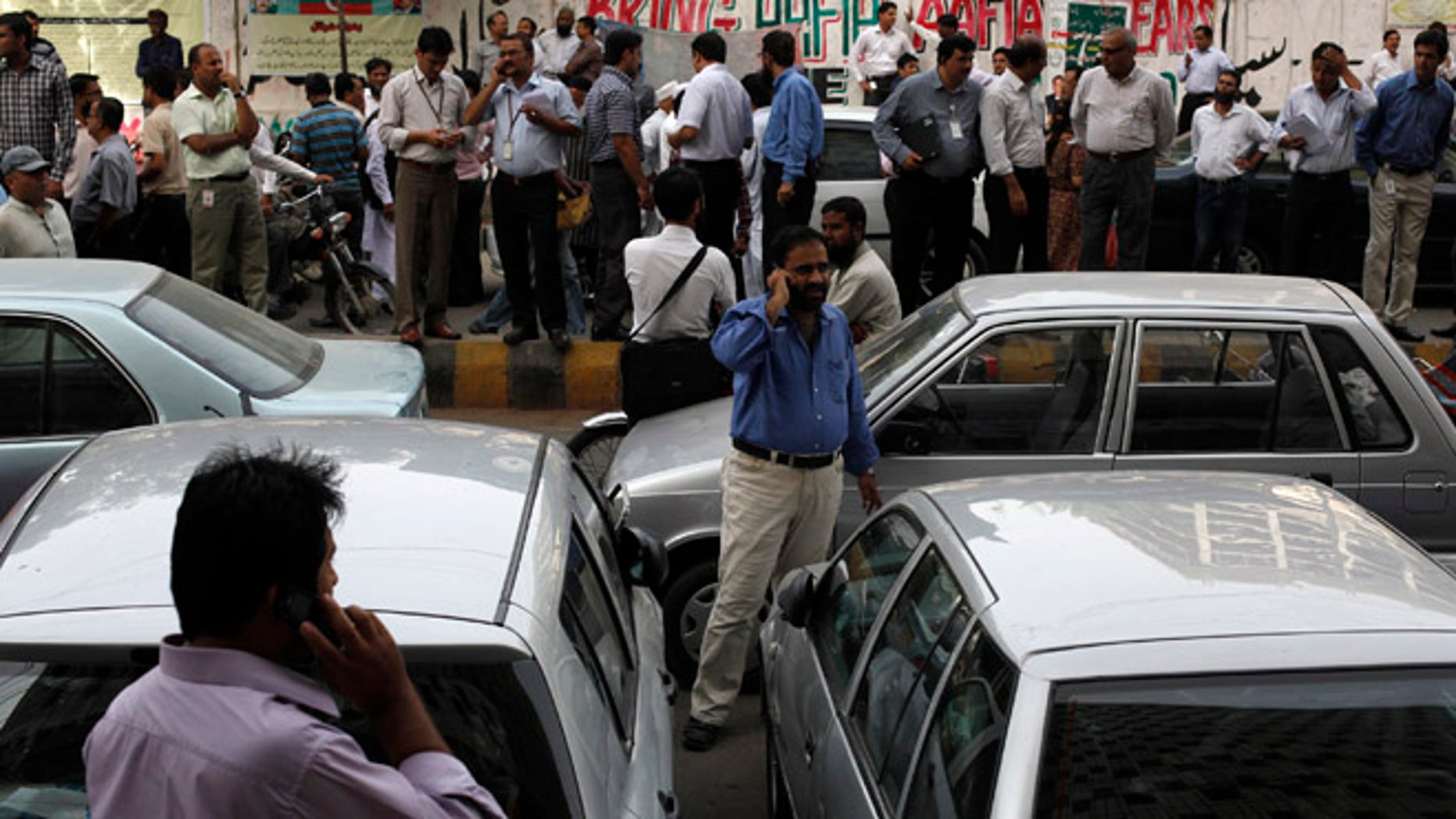April 16, 2013: Office workers stand outside of their buildings following an earthquake tremor in Karachi. An magnitude 7.8 earthquake struck Iran on Tuesday with tremors felt across Pakistan among other regions, media reported.