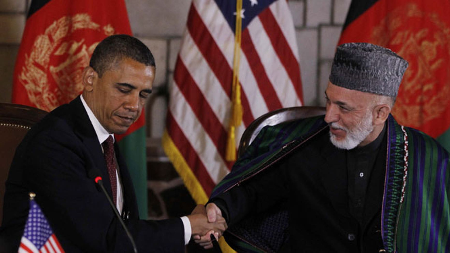 May 2, 2012: President Barack Obama and Afghan President Hamid Karzai shake hands after making statements before signing a strategic partnership agreement at the presidential palace in Kabul, Afghanistan.