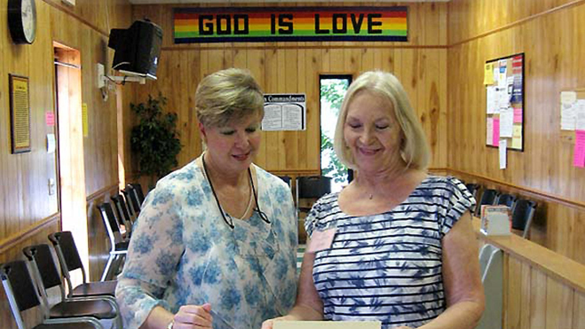 Christian Services Center Executive Director Kay Daly, left, works with a volunteer.